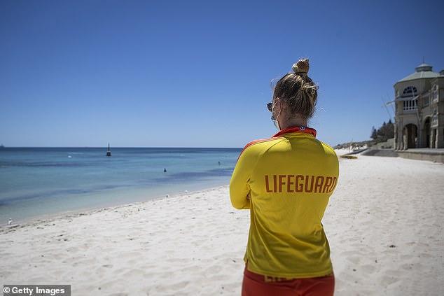 حارس يراقب شاطئ كوتيسلو المهجور في بيرث يوم الاثنين. على الرغم من ارتفاع درجات الحرارة في المدينة إلى 36 درجة مئوية ، كانت الشواطئ خالية في أول يوم كامل من الإغلاق المفاجئ